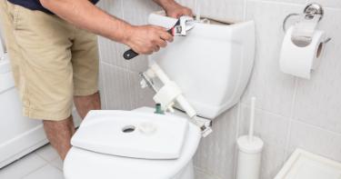 man fixing toilet