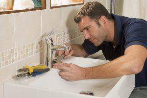 plumber installing a bathroom sink faucet